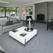 The Moorings in Taupo by Haimes Building - floor, flooring, furniture, interior design, living room, real estate, room, table, wood flooring, gray