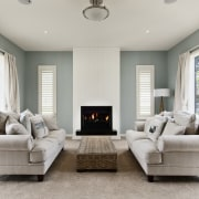 fireplace between two couches, green and white walls couch, floor, furniture, home, interior design, living room, loveseat, property, real estate, room, window, gray