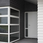 Exterior of single-storey house, dark stone cladding, and building, door, facade, home, house, siding, window, gray, black
