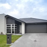 Exterior of single-storey house, dark stone cladding, and building, elevation, estate, facade, home, house, property, real estate, residential area, roof, siding, suburb, white, gray