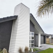 Exterior of single-storey house, dark stone cladding, and architecture, building, cottage, facade, home, house, property, real estate, residential area, siding, window, white