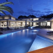 Made for laid-back entertaining  this resort-style landscape architecture, condominium, estate, home, hotel, house, leisure, lighting, mansion, property, real estate, reflection, resort, resort town, sky, swimming pool, villa, blue