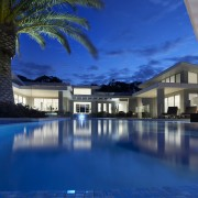 This home's landscape was designed by Dean Herald architecture, condominium, estate, evening, home, hotel, house, leisure, lighting, mansion, property, real estate, reflection, resort, resort town, sky, swimming pool, villa, water, blue