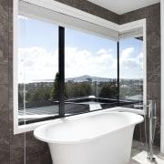 Positioned beneath a low window, the freestanding tub architecture, bathroom, bathtub, interior design, plumbing fixture, window, white