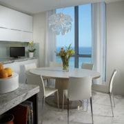 This breakfast area in a remodelled Miami apartment chair, dining room, interior design, living room, room, table, window, gray