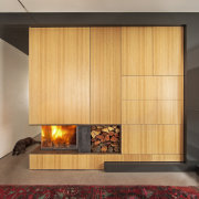 Oak cabinetry surrounds this contemporary fireplace. The house fireplace, floor, flooring, hearth, interior design, living room, wood, orange, gray