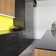 A bright yellow splashback is a feature of architecture, cabinetry, countertop, floor, house, interior design, kitchen, product design, room, gray