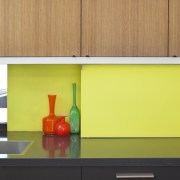 A bright yellow splashback is a feature of countertop, interior design, kitchen, orange, product design, shelf, shelving, table, wall, yellow, orange, yellow
