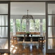 Sliding glass doors with reeded glass separate the dining room, door, furniture, home, house, interior design, table, window, gray, black