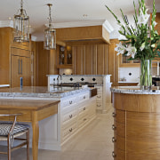 The larger island in this kitchen has an cabinetry, countertop, cuisine classique, interior design, kitchen, room, brown, gray