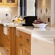 A close up view of the kitchen cabinetry. cabinetry, countertop, cuisine classique, furniture, interior design, kitchen, room, white, orange