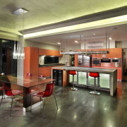 Bright orange cabinetry provides a contrasting highlight to ceiling, countertop, floor, flooring, interior design, kitchen, real estate, brown