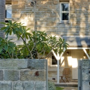This renovated sandstone terrace is one of a architecture, backyard, cottage, courtyard, estate, facade, home, house, landscaping, neighbourhood, outdoor structure, property, real estate, residential area, siding, stone wall, wall, window, gray