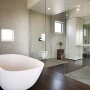 The sleek, custom-designed Minosa stone vanity in this architecture, bathroom, floor, flooring, home, interior design, plumbing fixture, product design, real estate, room, sink, tile, gray