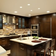 Understated dark wood cabinetry and cream countertops are cabinetry, countertop, cuisine classique, interior design, kitchen, orange, red