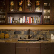 The spacious scullery in this traditional kitchen includes cabinetry, countertop, furniture, home, interior design, kitchen, kitchen organizer, lighting, room, shelf, shelving, under cabinet lighting, brown