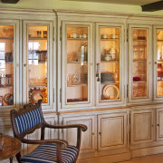 Cabinets in this traditional Provencal-style kitchen has a bookcase, cabinetry, cupboard, dining room, display case, door, furniture, interior design, living room, room, shelf, shelving, window, orange, brown