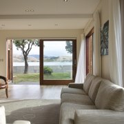 The expansive living space in this seaside home door, estate, home, house, interior design, living room, property, real estate, window, gray, brown