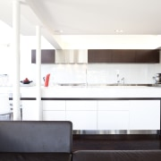 A large island bench extends into a cantilevered countertop, interior design, kitchen, real estate, room, white