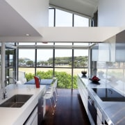 This light-filled galley-style kitchen is orientated to harness architecture, countertop, daylighting, house, interior design, kitchen, real estate, window, gray, white