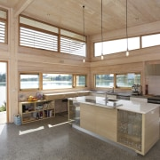 The island of this modern open-plan kitchen incorporates architecture, countertop, daylighting, house, interior design, kitchen, real estate, window, wood, white