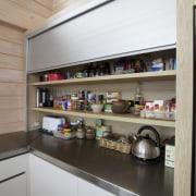 An aluminium door conceals the appliance garage and interior design, shelf, shelving, gray