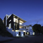 This modern four-level house steps down a steep apartment, architecture, building, condominium, corporate headquarters, facade, home, house, mixed use, property, real estate, residential area, sky, blue, black