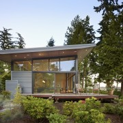 The new waterfront house is largely transparent on architecture, cottage, facade, home, house, outdoor structure, property, real estate, roof, siding, brown