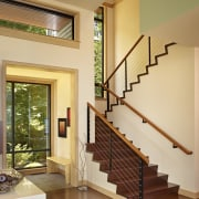 The stairway to the master suite is beside architecture, ceiling, floor, handrail, hardwood, home, house, interior design, living room, real estate, stairs, wall, window, orange, brown