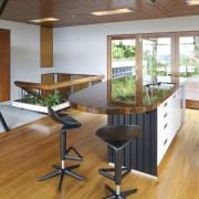 Architect John Mills introduced a large island to countertop, floor, flooring, furniture, hardwood, interior design, kitchen, laminate flooring, real estate, table, wood, wood flooring, brown