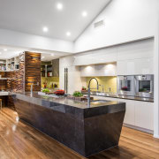 This kitchen features a large marble-clad island. The ceiling, countertop, floor, flooring, hardwood, interior design, kitchen, laminate flooring, living room, wood, wood flooring, white