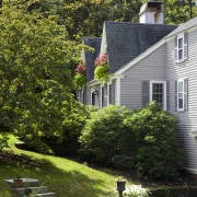 This Cape Cod-style residence was built in 1768, architecture, backyard, cottage, estate, farmhouse, garden, grass, home, house, landscape, landscaping, lawn, leaf, neighbourhood, outdoor structure, plant, property, real estate, residential area, siding, suburb, tree, walkway, yard, brown