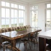 In this traditional lakefront house casual dining is chair, dining room, furniture, home, interior design, room, table, window, white