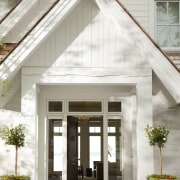 Weathered beams and columns impart a sense of door, facade, home, house, white