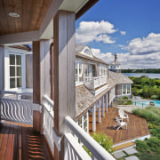 The generous decking, French doors and uniform white apartment, balcony, cottage, deck, estate, home, house, outdoor structure, porch, property, real estate, residential area, siding, window, wood, gray