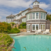 On this traditional Cape Cod house, a playful building, cottage, estate, facade, home, house, mansion, property, real estate, reflection, residential area, sky, villa, water, teal