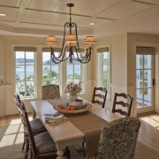 In this Cape Cod home, the adjacent dining dining room, door, estate, home, interior design, living room, real estate, room, window, brown