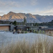 This house achieves privacy from the street by home, house, lake, landscape, mountain, mountain range, mountainous landforms, property, real estate, reflection, sky, tree, water, wilderness, winter, gray