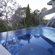 Designed by Dean Herald of Rolling Stone Landscapes, architecture, estate, home, house, leisure, lighting, property, real estate, reflection, resort, swimming pool, tree, water, blue