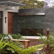 A slumped glass water feature on a bluestone-clad architecture, arecales, backyard, courtyard, estate, facade, garden, home, house, landscaping, plant, property, real estate, residential area, yard, brown, gray