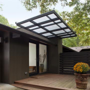 This prefabricated post-and-beam house has been transformed by backyard, house, outdoor structure, roof, black