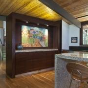 A freestanding wood divider separates key areas in architecture, ceiling, floor, flooring, hardwood, home, house, interior design, laminate flooring, living room, lobby, real estate, wall, wood, wood flooring, brown