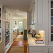This kitchen blends with its surroundings through architectural bookcase, cabinetry, furniture, home, interior design, kitchen, living room, room, shelf, shelving, gray