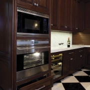 In this kitchen remodel, the cabinets are chock cabinetry, countertop, floor, flooring, furniture, hardwood, home appliance, kitchen, kitchen appliance, oven, wood, black