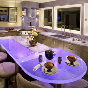 Glass benchtops illuminated with violet lighting ensure this countertop, interior design, kitchen, purple, room, brown