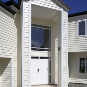 Namu Construction remodelled this expansive home with James building, door, elevation, facade, home, house, property, real estate, residential area, siding, window, white, gray