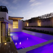 Landscape designer Fiona Kelly converted a walkway into architecture, estate, home, house, light, lighting, property, real estate, reflection, residential area, sky, swimming pool, purple