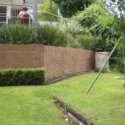 Because of its proximity to the interior living backyard, fence, garden, grass, grass family, landscape, landscaping, lawn, outdoor structure, plant, property, real estate, tree, walkway, wall, yard, green