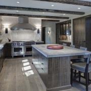 In this kitchen remodel by Doug Durbin, the countertop, floor, flooring, interior design, kitchen, gray, black