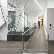 A multifaceted facade behind the reception desk of architecture, daylighting, floor, flooring, glass, handrail, interior design, product design, stairs, tourist attraction, white, gray